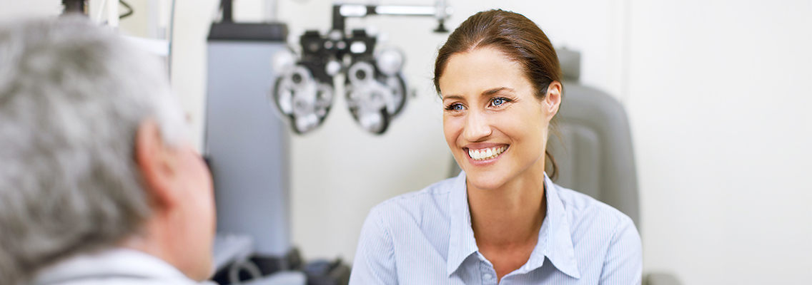woman smiling at an eye care practitioner
