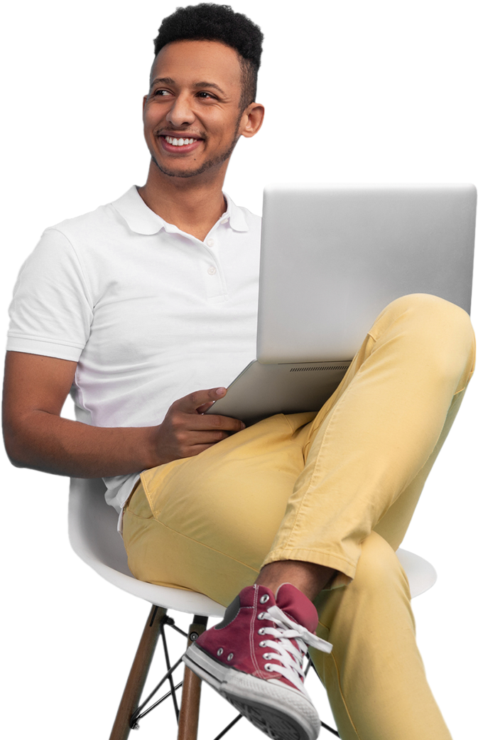 man smiling and holding a laptop