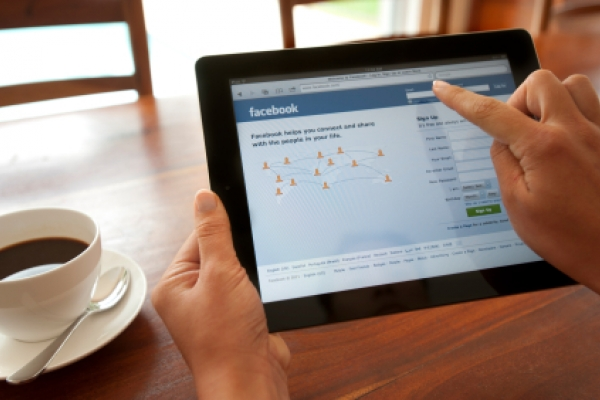 Woman holding an iPad with Facebook login.