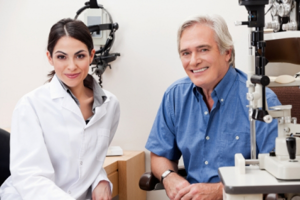 Smiling female optometrist with patient