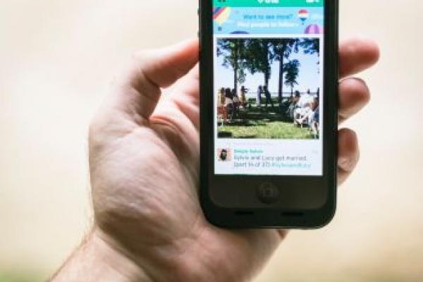 Hand holding a smartphone with Vine app open