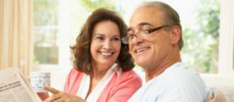 mature couple smiling and reading a newspaper