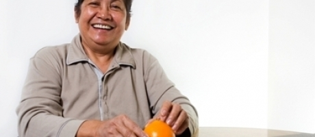 mature woman smiling and peeling an orange