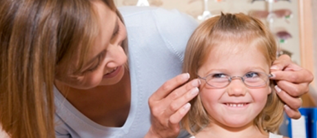 young girl trying on glasses at eye examination