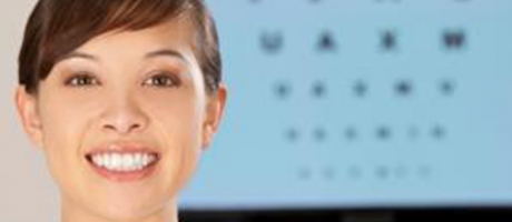 woman smiling next to eye chart