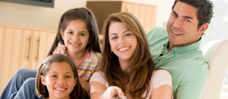 family smiling and watching television