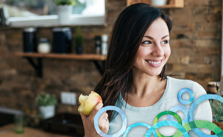 woman smiling and holding an apple in a kitchen
