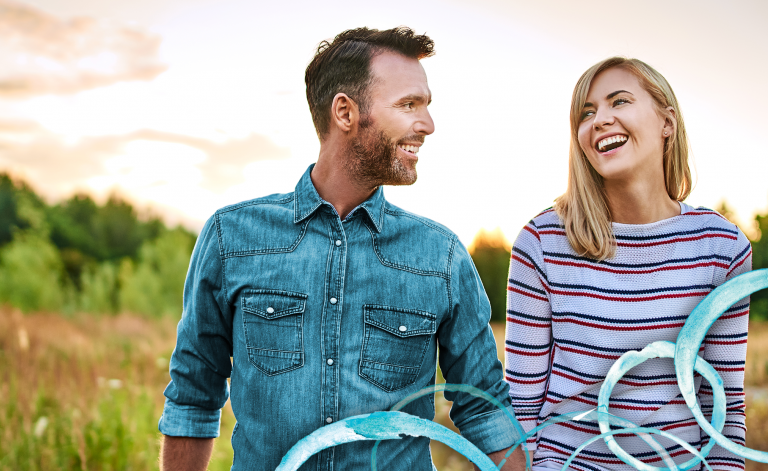 man and woman smiling outdoors