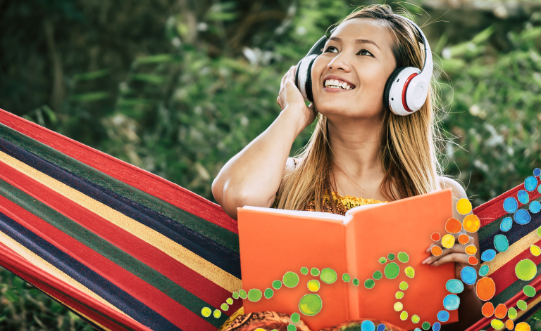 woman smiling with headphones and holding a book