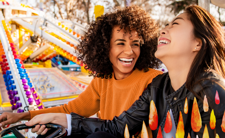 women smiling on a ride at the fair